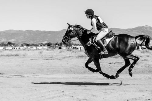 Black and white of horse and rider running